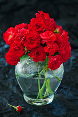 Beautiful red roses in a vase on a table. dark background .