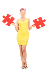 Trendy girl holding two pieces of a puzzle