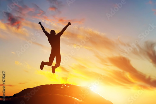 Happy man jumping for joy on the peak of the mountain. Success