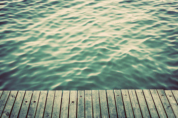 Grunge wood boards of a pier over ocean, rippling waves. Vintage
