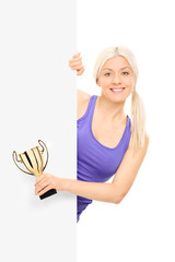Female athlete holding a trophy behind a panel