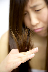 Asian woman unhappy about split ends hair