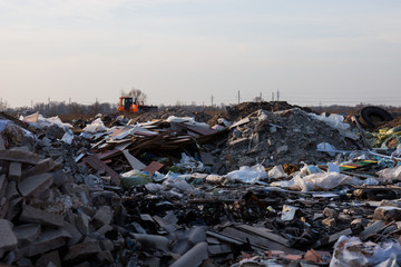Garbage on the landfill and working bulldozer