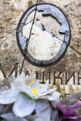 Damaged portrait of the buried person on the old gravestone