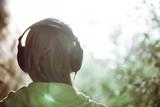 Fototapety Woman in headphones against bright sunlight