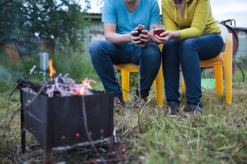 Couple with tea cups in hands near the smouldering fire