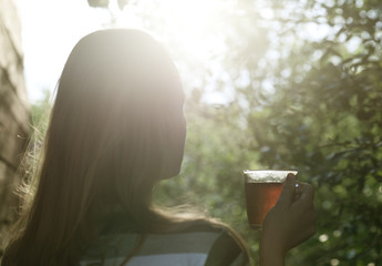 Woman with cup of tea in evening sunlight