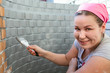 Woman with paint brush in hands painting a brick wall