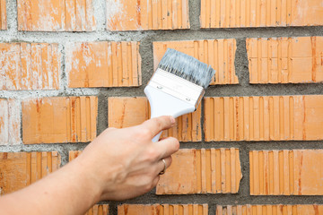 Caucasian hand starting to paint brick wall