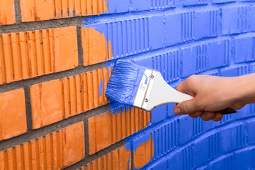 Human hand painting wall with blue color