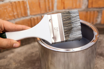 Human hand holding paint brush stained grey color