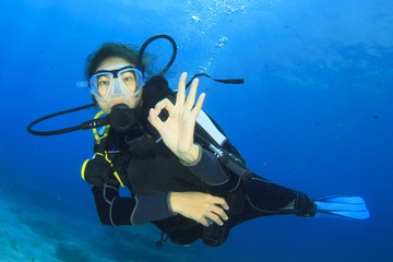 Young woman scuba diving signals okay