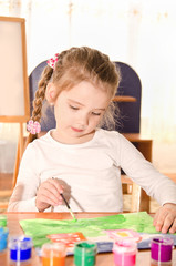 Cute little girl drawing with paint