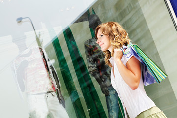 Young woman standing near a shop window with shopping bags.