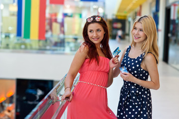 two woman friends in shopping mall with credit cards