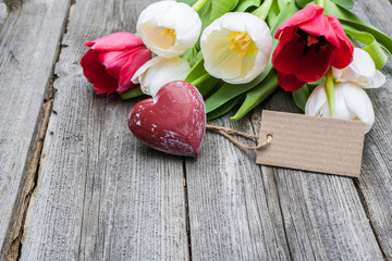 fresh tulips and red heart with a tag