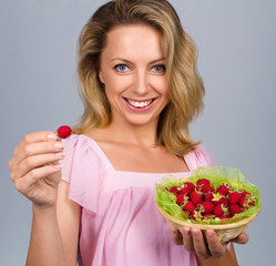 Smiling woman holding raspberries
