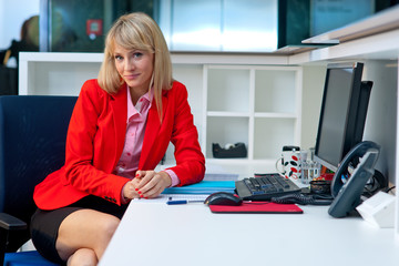 attractive blond woman in office sitting