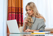 attractive blond woman writing on laptop