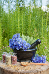mortar with blue cornflowers and sage, herbal medicine