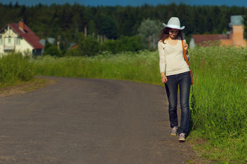 Background girl goes right along countryside road in a cowboy ha