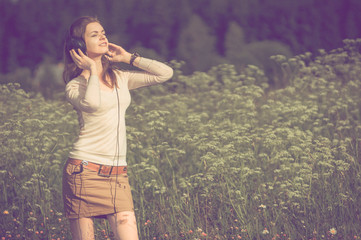 background girl standing in a grassy field in headphones and lis