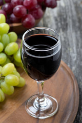 glass of red wine and grapes on a wooden board