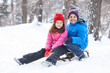 two children prepared to slide from hill.