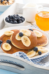 pancakes with banana, honey and blueberries