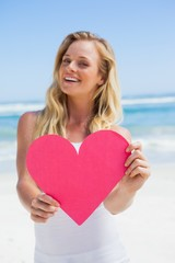 Smiling blonde showing pink heart on the beach