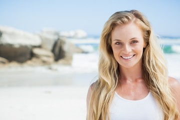 Gorgeous blonde smiling at camera on the beach
