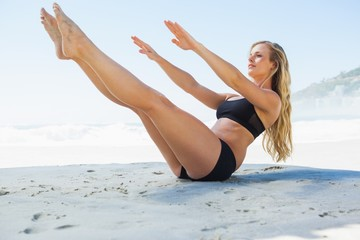 Fit blonde in core balance pilates pose on the beach