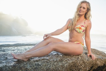 Gorgeous blonde in floral bikini sitting on a rock at beach