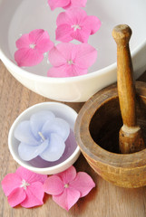 Flowers in a water bowl with candle and a wooden pestle