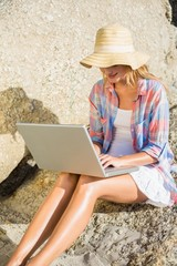 Pretty blonde using laptop at the beach