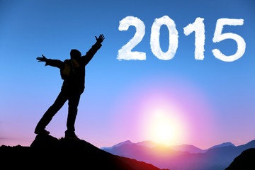 happy new year 2015.young man standing on the top of mountain