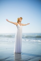 Smiling blonde standing on the beach in white sundress and sunha