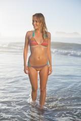 Happy blonde standing by the sea posing in bikini