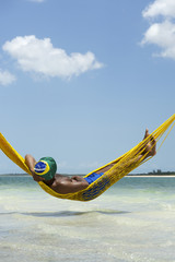 Brazilian Man Relaxing in Beach Hammock Over Sea