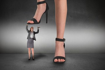 Composite image of female feet in black sandals standing on busi