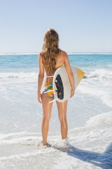 Fit surfer girl standing in the sea with her surfboard