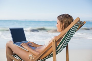 Woman relaxing in deck chair on the beach using laptop
