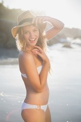 Beautiful happy blonde looking at camera at the beach