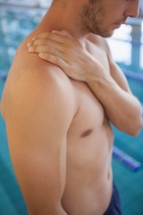 Fit swimmer standing by the pool touching his shoulder