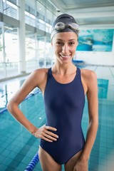 Pretty swimmer standing by the pool smiling at camera