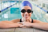 Fit swimmer in the pool smiling at camera