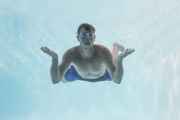 Man shrugging shoulders underwater in swimming pool