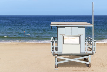 Wood lifeguard tower facing ocean, male person paddle boarding