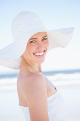 Pretty smiling blonde in white dress and sunhat on the beach