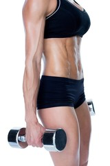 Female bodybuilder working out with large dumbbells mid section